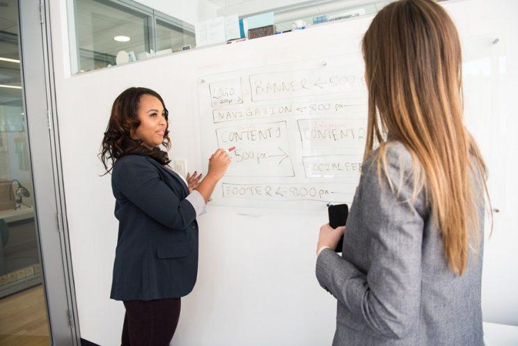 mulher numa startup ensinando passos de negócios a sua funcionária